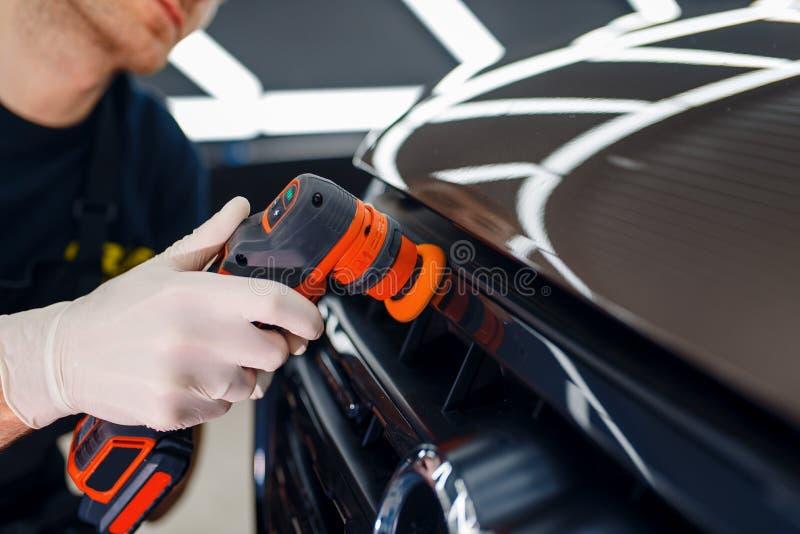 Il lavoratore lucida la griglia del radiatore, con dettagli sull'auto immagini stock