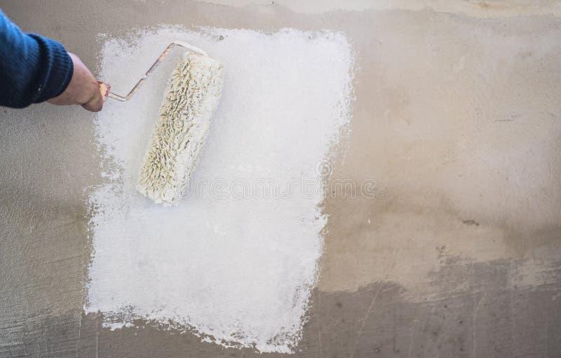 Il lavoratore manuale dipinge il bianco della parete con il rullo del pittore, primo piano fotografia stock