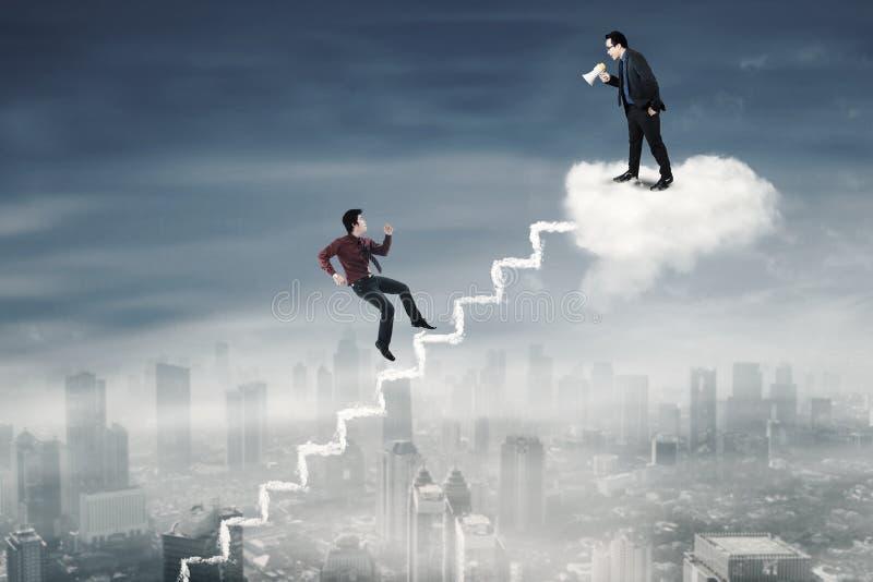 Il lavoratore maschio incontra il suo capo sulla nuvola immagini stock