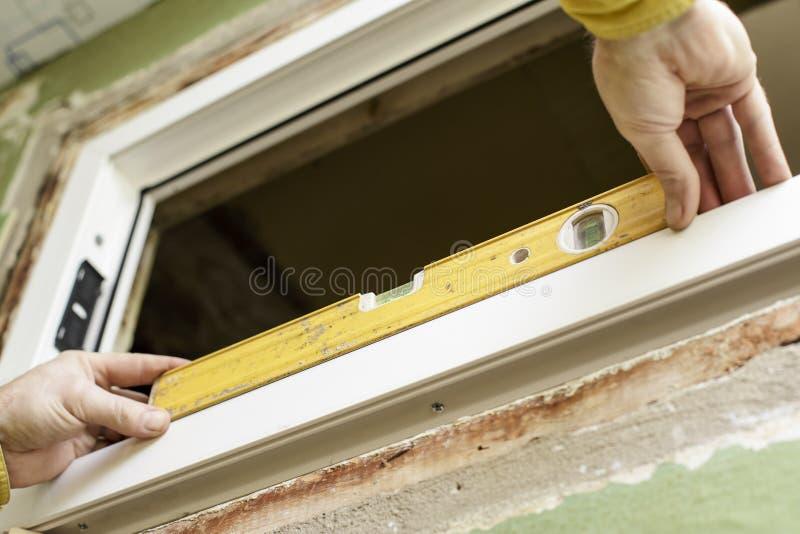 Il lavoratore maschio installa UPVS la finestra facendo uso del livello fotografie stock libere da diritti