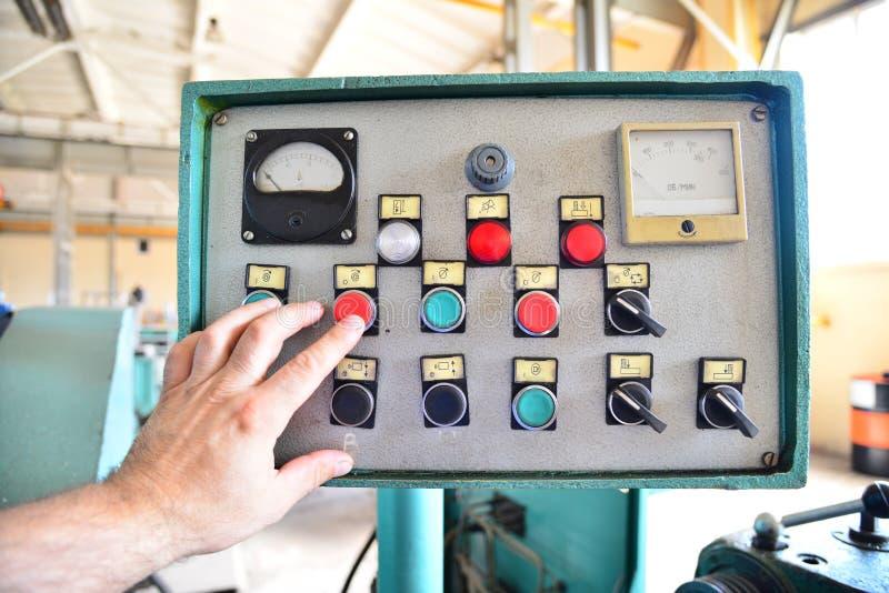 Il lavoratore preme i bottoni e le attrezzature telecomandate della macchina nell'impresa immagine stock