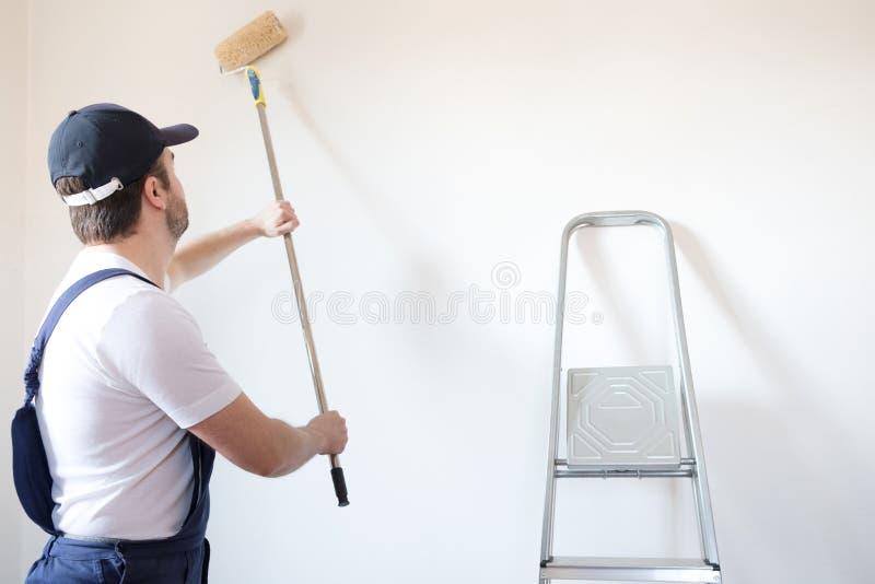 Il lavoratore professionista del pittore sta dipingendo la parete fotografia stock