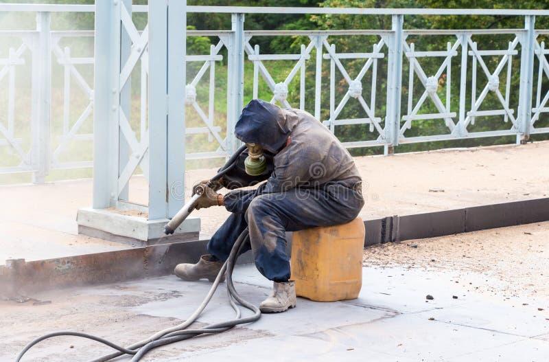Il lavoratore pulisce le costruzioni metalliche che sabbiano lo strumento immagine stock libera da diritti