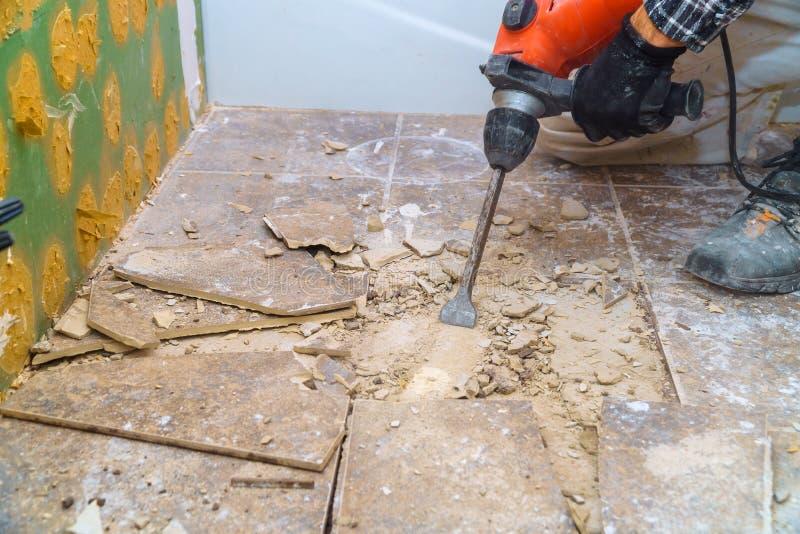 Il lavoratore rimuovere, demolisce le vecchie mattonelle un bagno con il martello pneumatico immagini stock
