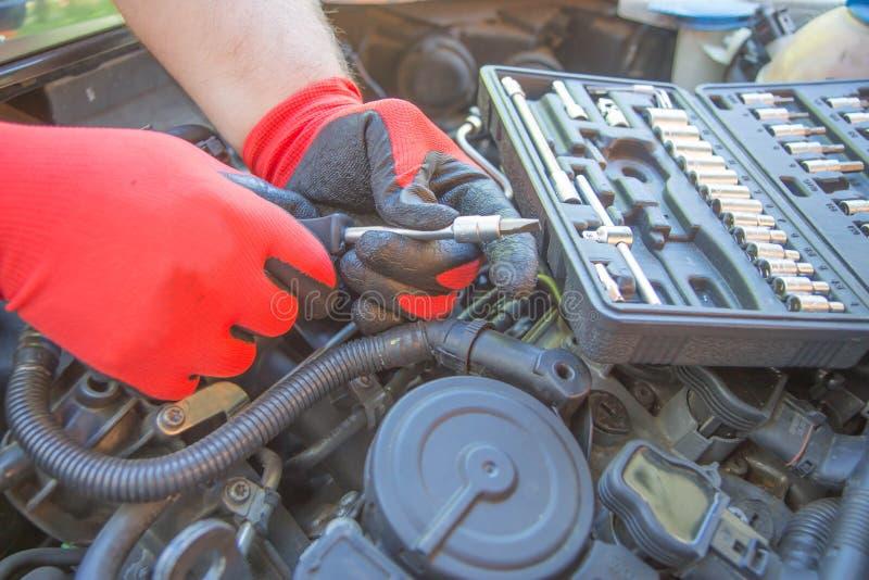 Il lavoratore ripara un'automobile in un centro della riparazione dell'automobile Servizio di riparazione Manutenzione di automob fotografia stock