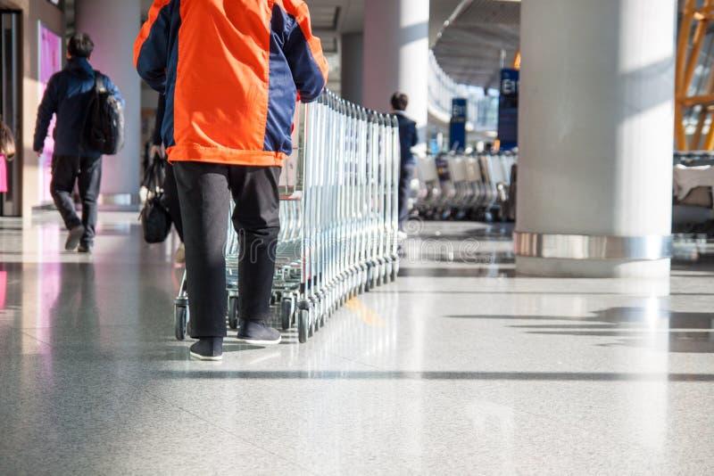 Il lavoratore rotola una pila di carrelli del bagaglio nell'area di partenza dell'aeroporto fotografie stock libere da diritti