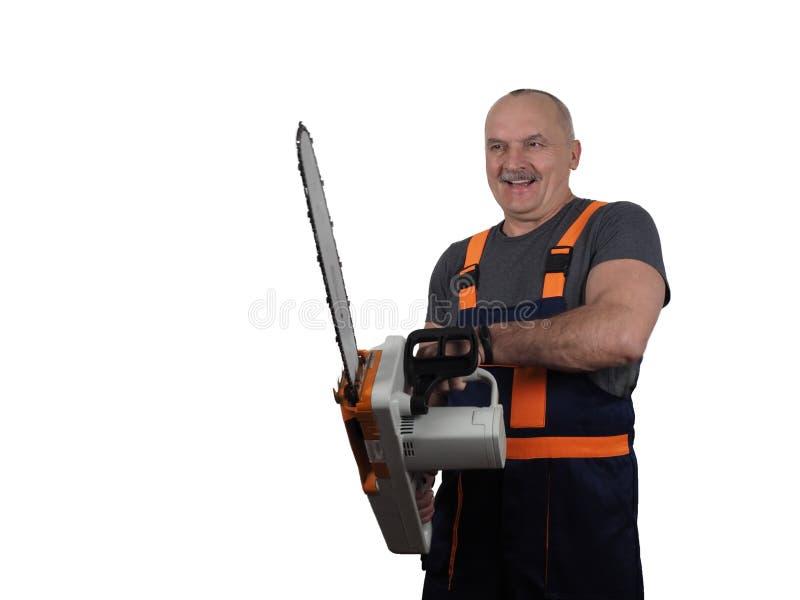 Il lavoratore senior con la sega elettrica immagine stock