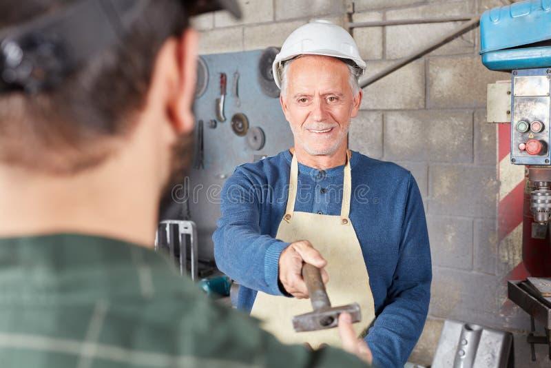 Il lavoratore senior dà il martello al collega fotografie stock libere da diritti