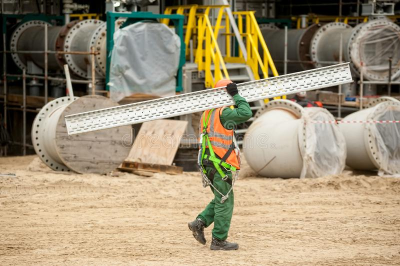Il lavoratore sopporta il materiale da costruzione sullo stabilimento chimico immagine stock libera da diritti