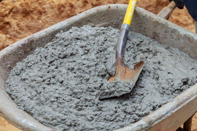 Il lavoratore spala un miscuglio umido di calcestruzzo dalla carriola all'installazione del blocchetto del bordo immagine stock libera da diritti