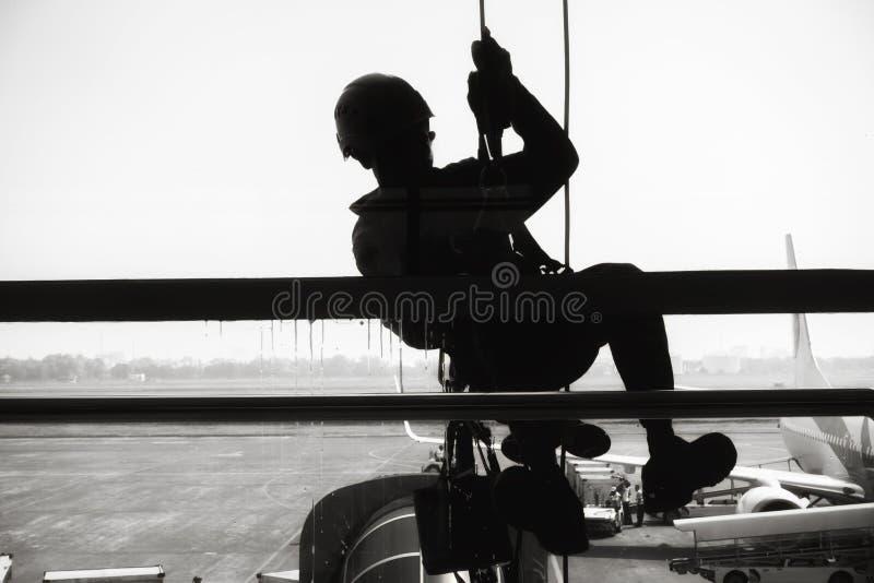 Il lavoratore sta pulendo di vetro di finestre nel terminale di aeroporto , La siluetta dell'impiegato rappelling per la strofina immagini stock