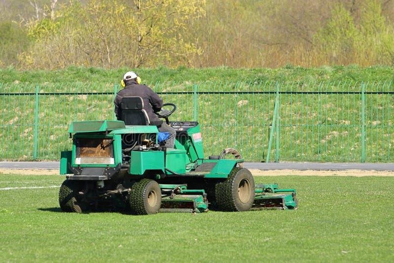 Il lavoratore su una grande falciatrice da giardino verde falcia l'erba sul campo di football americano Architettura del p?saggio immagini stock libere da diritti