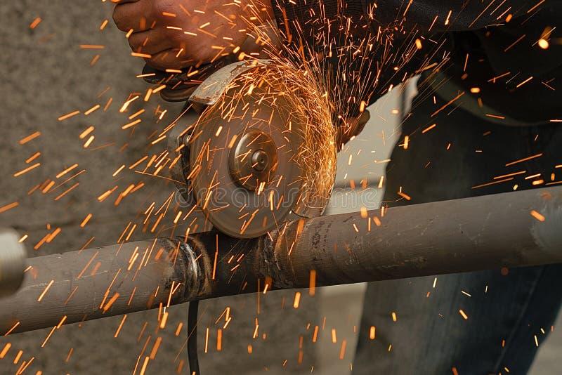 Il lavoratore taglia un tubo del metallo per mezzo dello strumento abrasivo fotografia stock libera da diritti