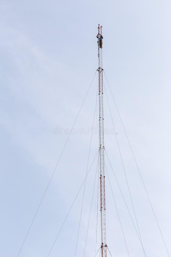 Il lavoratore tailandese sta lavorando all'alta torre di comunicazione fotografie stock libere da diritti