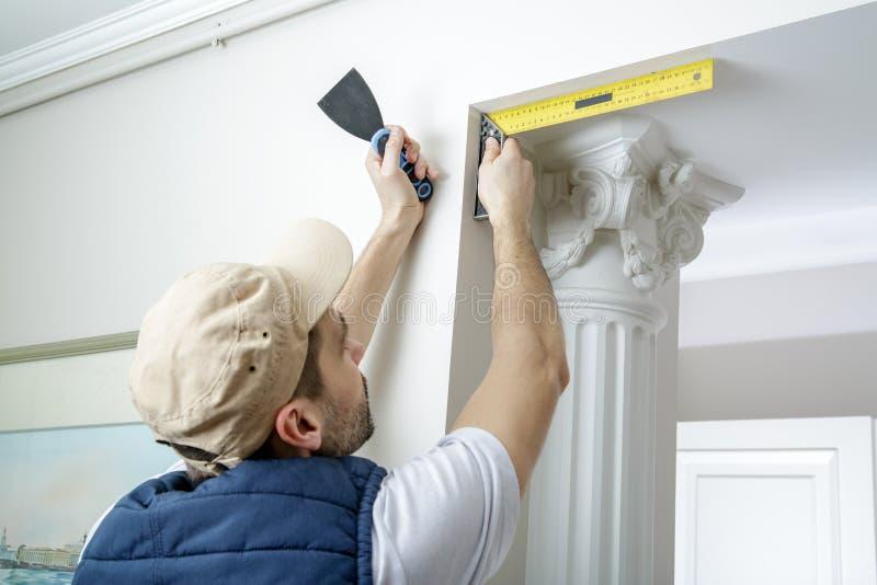 Il lavoratore tiene il coltello di mastice e misura l'angolo della parete facendo uso dell'angolo del metallo immagini stock libere da diritti