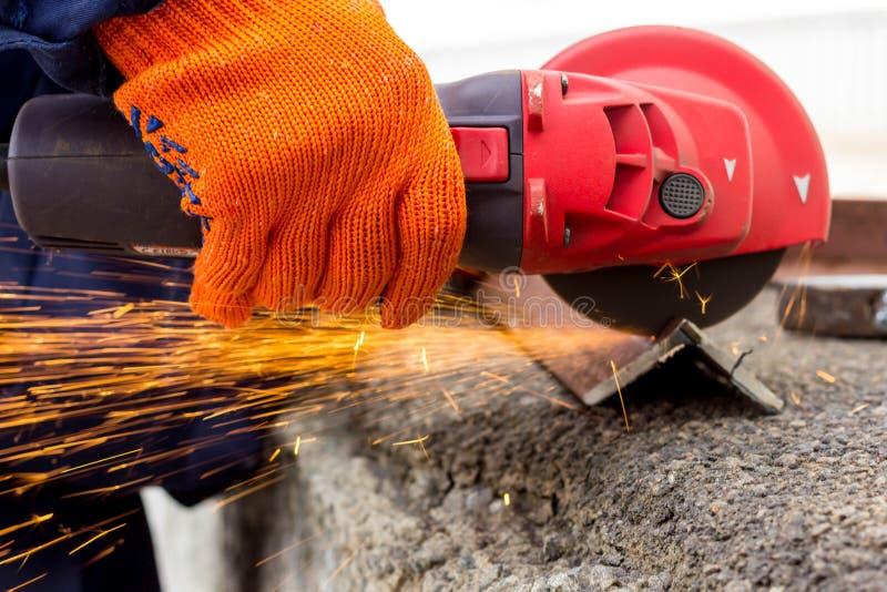 Il lavoratore usa una smerigliatrice dell'azionamento di angolo per lavorare con un angolo di metallo Smerigliatrice dell'azionam fotografia stock