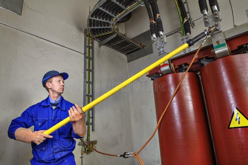 Il lavoratore utilizza il bastone d'isolamento a terra che collega il trasformatore a massa fotografia stock