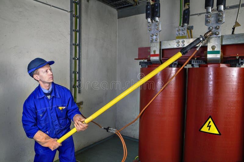 Il lavoratore utilizza la barretta d'isolamento a terra che collega il trasformatore a massa fotografie stock