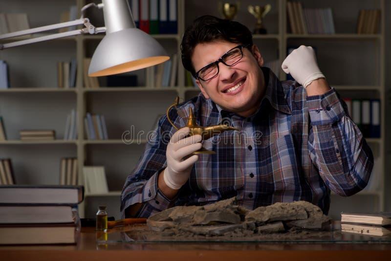 Il lavoro dell'archeologo a tarda notte in ufficio fotografia stock