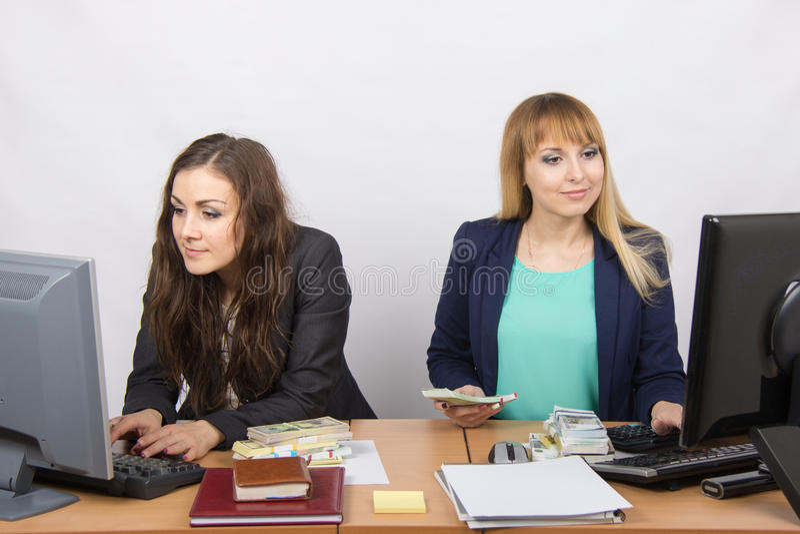 Il lavoro dello spazio ufficio con gli impiegati dei soldi due ad una tavola fotografia stock
