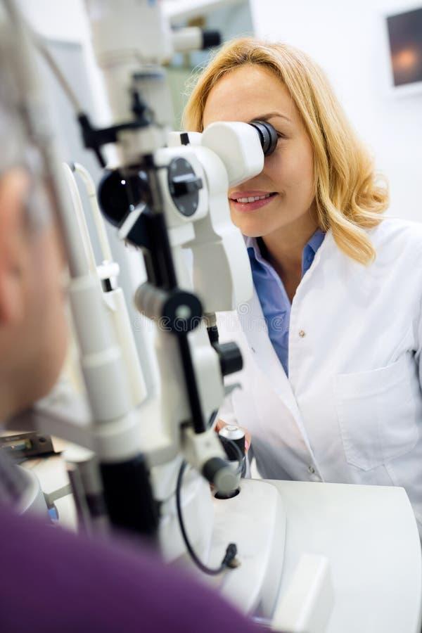 Il lavoro femminile di medico di occhi con l'apparato ed i controlli osserva per patien fotografie stock