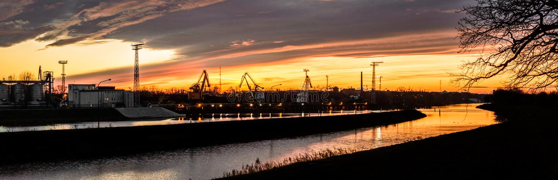 Il letto di fiume nel carbone che scarica zona nella centrale elettrica termica, tramonto fotografia stock libera da diritti
