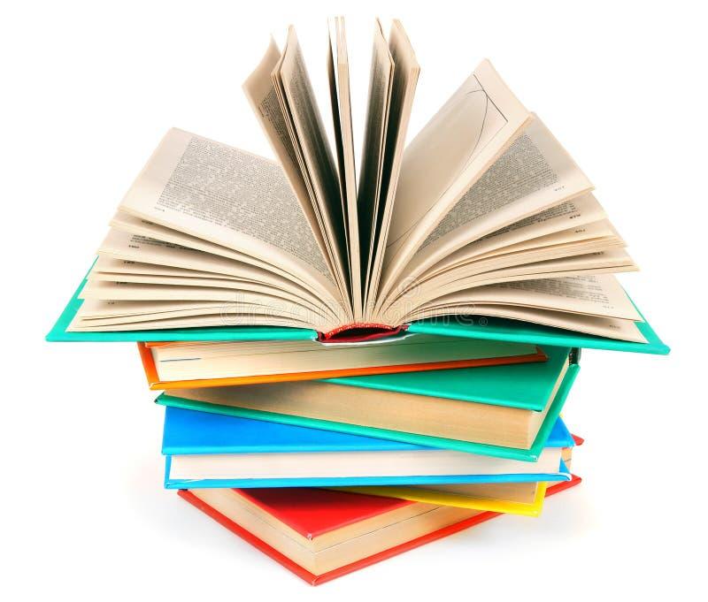 Il libro aperto su un mucchio dei libri multicolori immagini stock libere da diritti