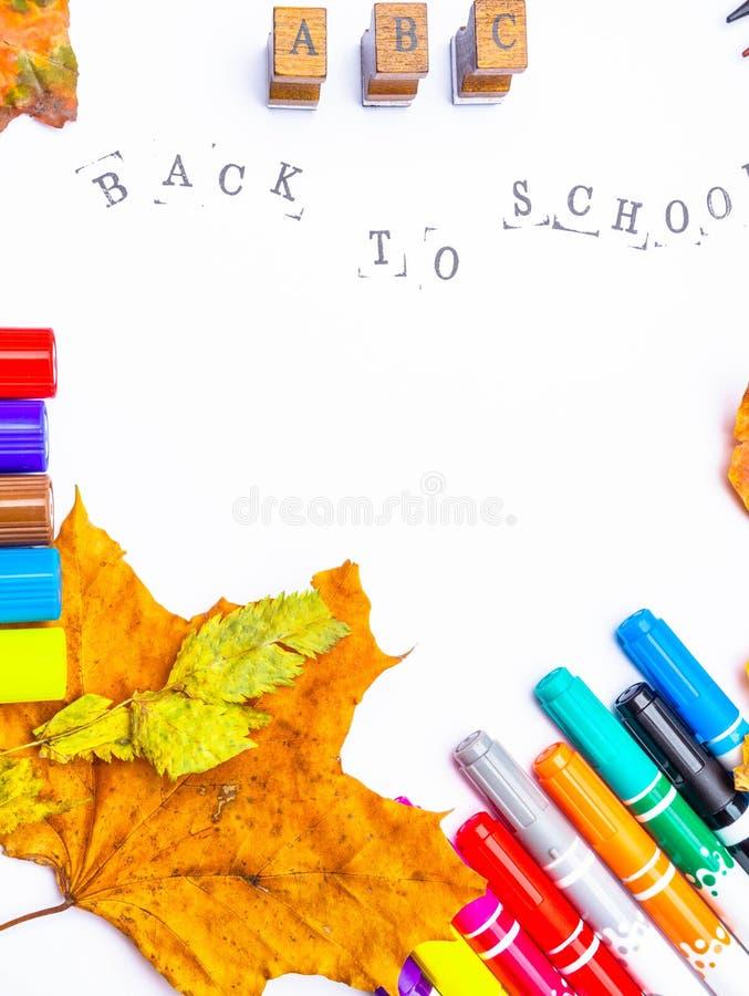 Il Libro Bianco con l'iscrizione timbrata di nuovo a scuola con gli indicatori, matite ha isolato immagini stock libere da diritti