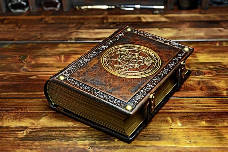 Il libro d'annata dell'alchimista con i bordi di carta dorati ed il simbolo indicano alla tavola di legno fotografia stock libera da diritti