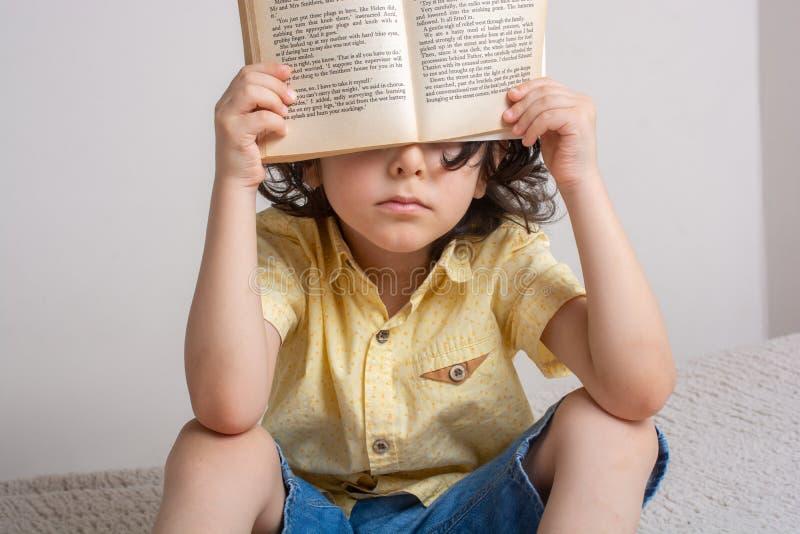 Il libro della tenuta del ragazzo sui suoi eyesas prenota il concetto del giorno fotografia stock libera da diritti