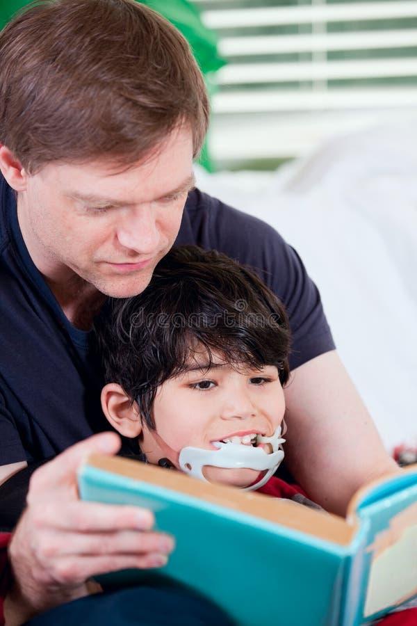 Il libro di lettura del padre ha disattivato il piccolo figlio fotografia stock libera da diritti