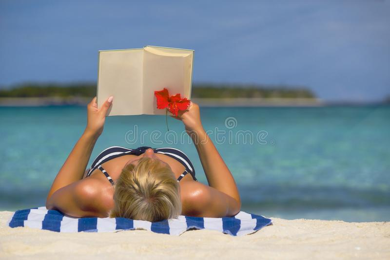 Il libro di lettura nella spiaggia passa il libro della tenuta con le pagine in bianco co immagine stock