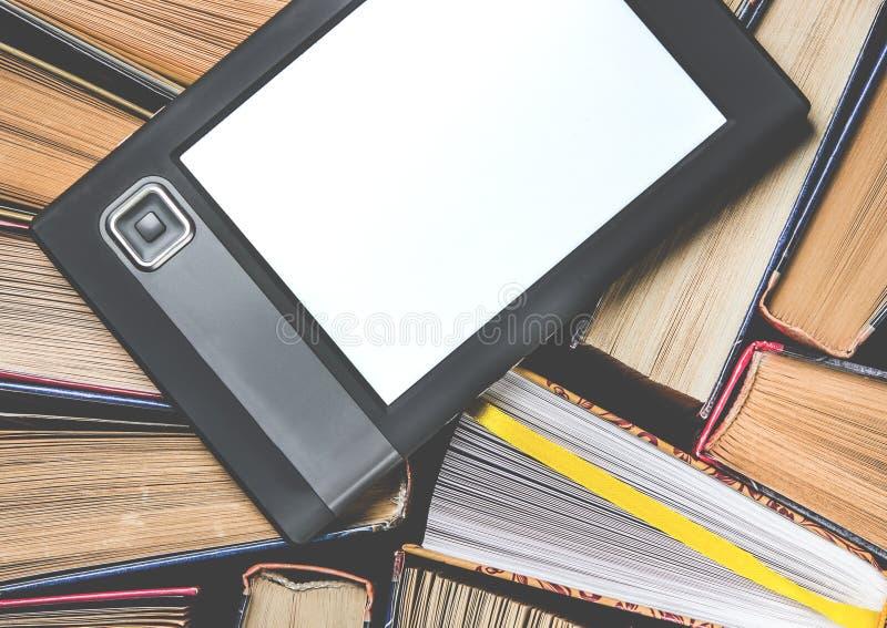 Il libro elettronico con uno schermo bianco si trova dei sui libri colorati multi aperti che si trovano su un fondo scuro, primo  immagini stock