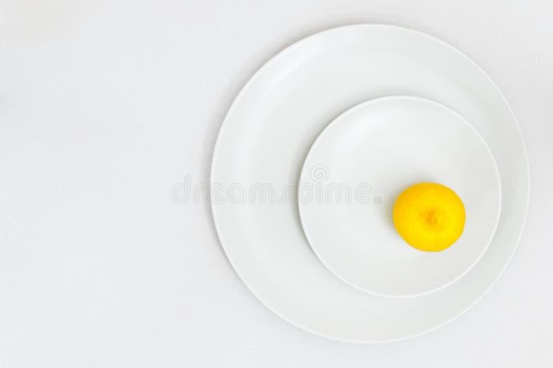 Il limone fresco su due piatti bianchi con carta ha strutturato il fondo fotografie stock
