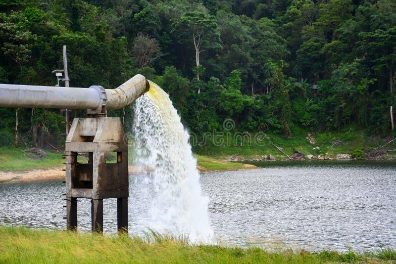 Il lotto dell'acqua che zampilla dal grande tubo del metallo al lago, l'acqua della pompa riempie il bacino idrico fotografie stock