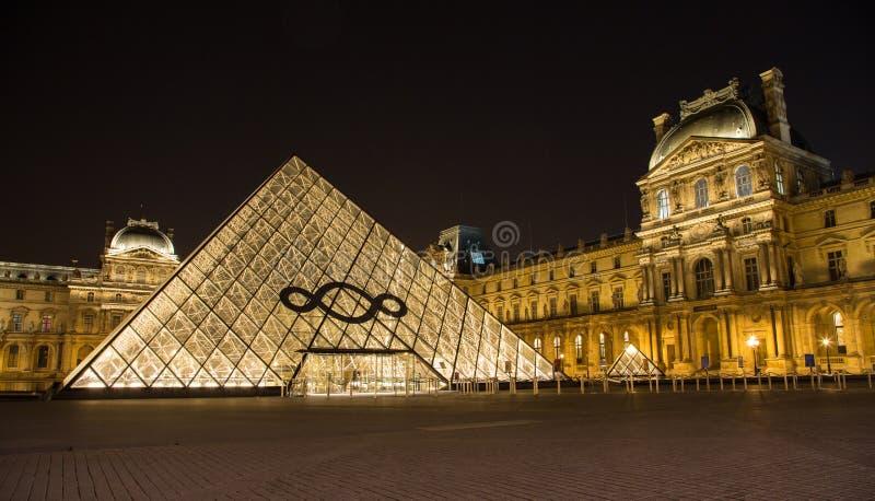 Il Louvre di Parigi in Francia di notte fotografia stock libera da diritti