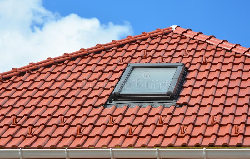 Il lucernario sulle mattonelle di tetto ceramiche rosse alloggia il tetto Lucernario moderno del tetto I lucernari della soffitta immagini stock libere da diritti