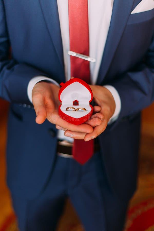 Il lusso bello ha vestito l'uomo in scatola in forma di cuore rossa della tenuta blu alla moda con le fedi nuziali Primo piano immagini stock