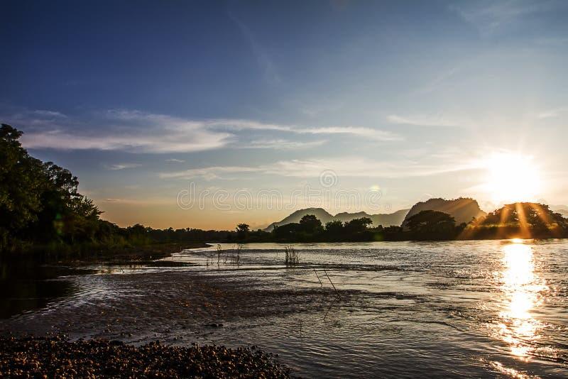 Il lustro del sole attraverso il fiume di sera nei precedenti fotografia stock