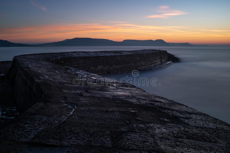 Il Lyme Regis Cobb, serpeggiante fuori al mare con il sole che aumenta sopra le colline distanti, esposizione lunga immagini stock