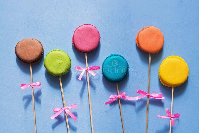Il macaron francese del biscotto su un bastone con un arco su un blu ha dipinto il fondo opera d'arte creativa fotografia stock libera da diritti