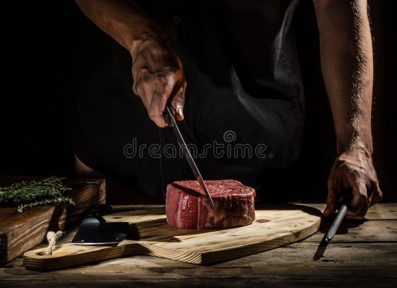 Il macellaio del cuoco unico prepara la bistecca di manzo immagine stock libera da diritti