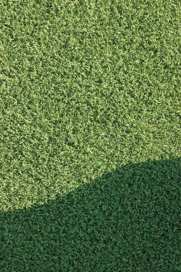 Il macro primo piano dell'erba di falsificazione del tappeto erboso del campo sintetico artificiale del prato inglese con area di immagine stock