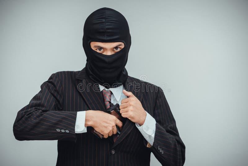 Il mafioso in vestito estrae una pistola prima del lavoro di rapina in banca fotografia stock libera da diritti