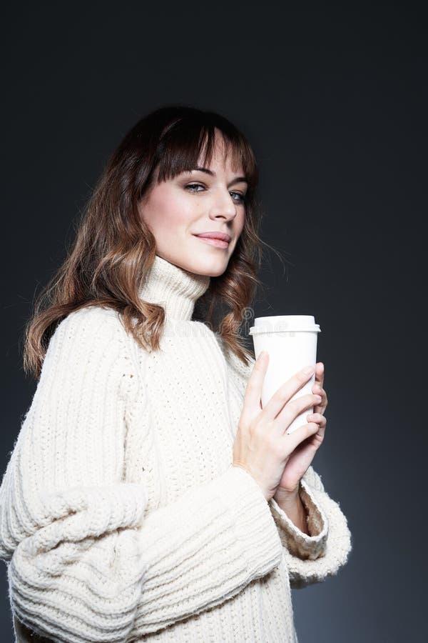Il maglione d'uso della bella donna tiene la tazza di caffè eliminabile di carta Bere il caffè, guarda alla macchina fotografica fotografia stock