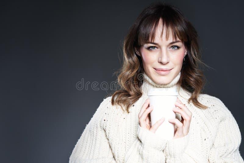 Il maglione d'uso della bella donna tiene la tazza di caffè eliminabile di carta Bere il caffè, guarda alla macchina fotografica immagine stock