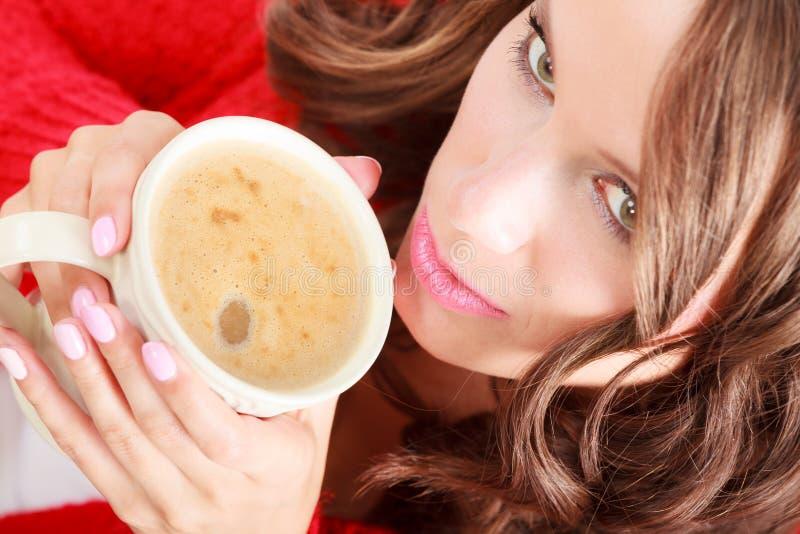 Il maglione rosso della ragazza tiene la tazza con caffè immagine stock