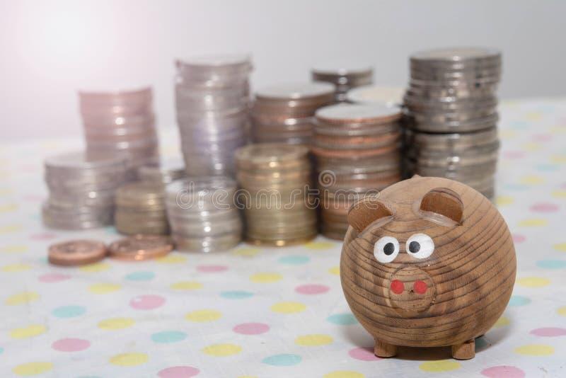 Il maiale di legno con la moneta impila il fondo, i concetti di risparmio dei soldi, concetti di investimento fotografie stock libere da diritti