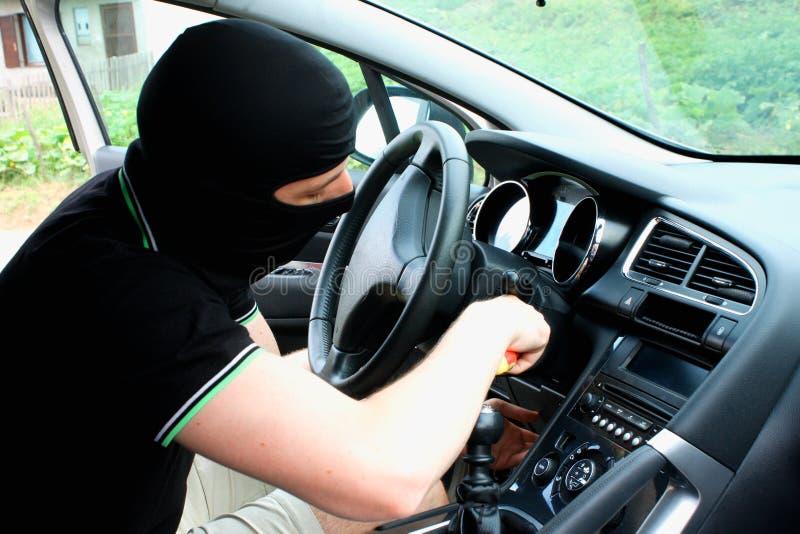 Il malfattore nella maschera che ruba automobile fotografie stock