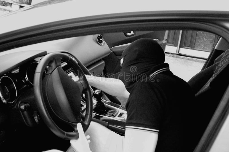 Il malfattore nella maschera che ruba automobile fotografia stock libera da diritti
